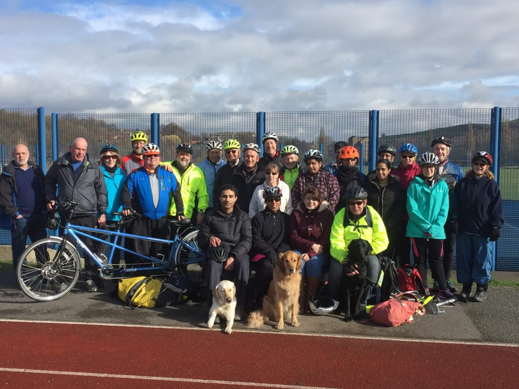 25 Trekkers and 3 Guide Dogs clustered around the bench at Leeds Road Track
